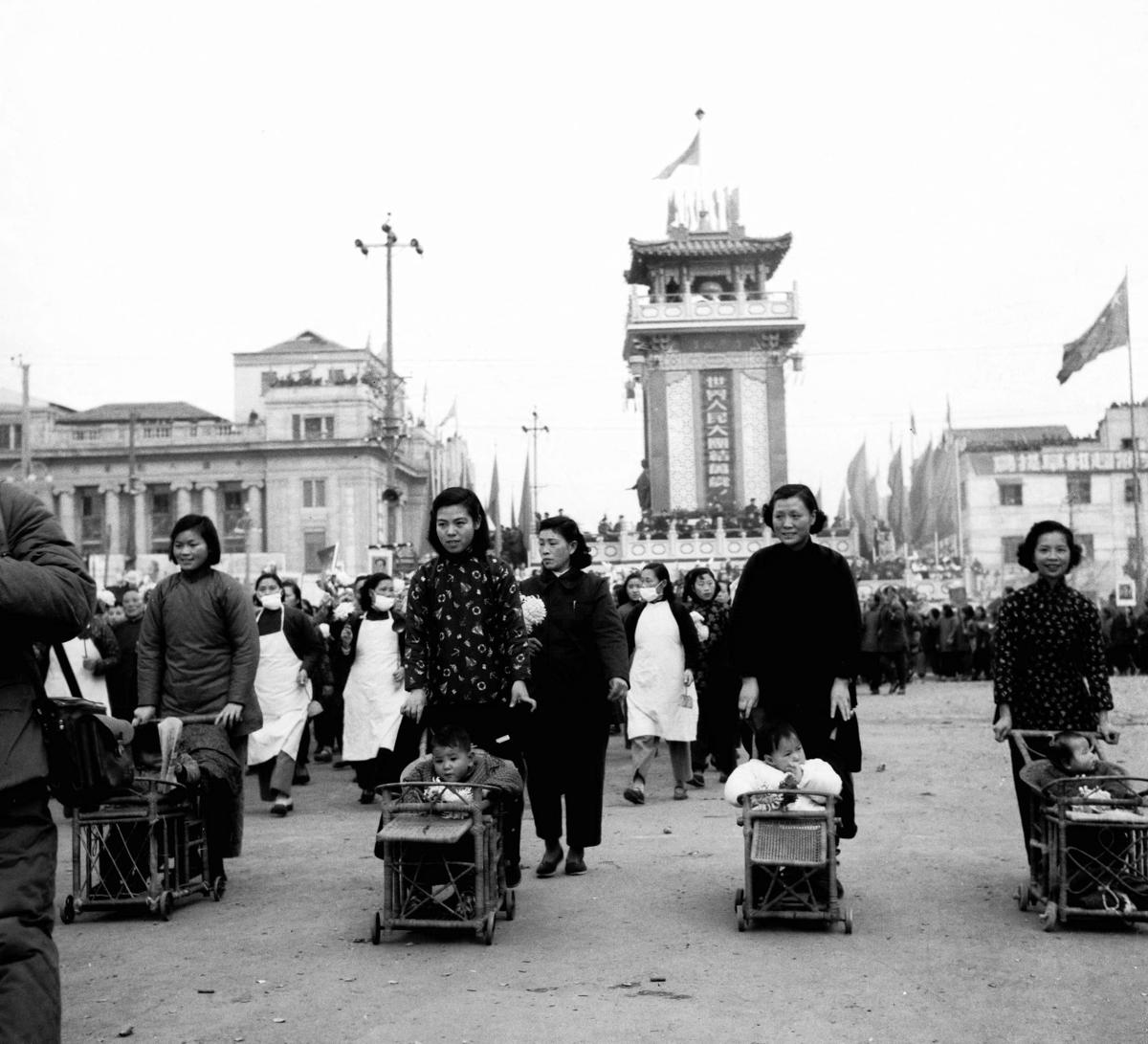 14-2 1954南京市隆重庆祝国庆节全市各行各业都由先进人物作为代表参加盛典活动,这是香铺營街道居民推着童车游行.jpg