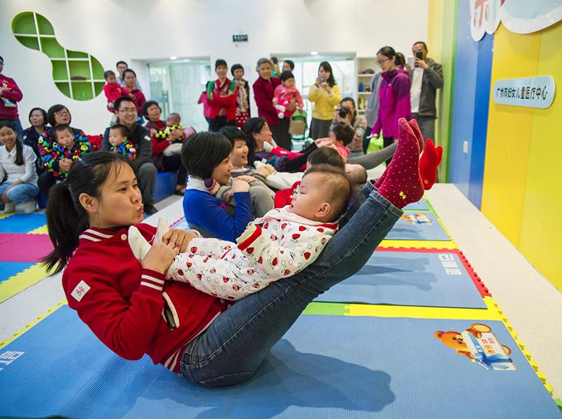 14-4 周宗毅《亲子瑜伽》拍摄时间2015.01.17,拍摄于广东省广州市珠江新城广州市妇女儿童医疗中心。在该中心出生的婴儿及其父母被邀请回来参加亲子运动会。在运动会上,母亲们和小宝宝玩起.jpg